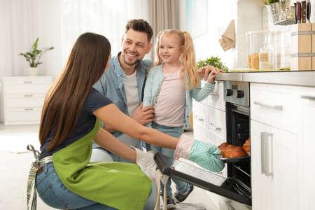 Frau und ihre Familie nehmen Tablett mit gebackenen Brötchen aus dem Ofen in der Küche heraus Standard-Bild