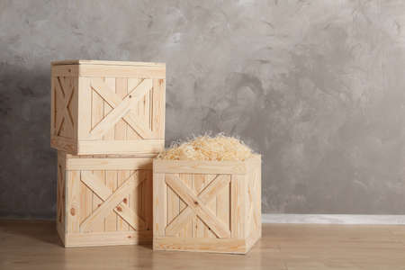 Wooden crates on floor against color background, space for text