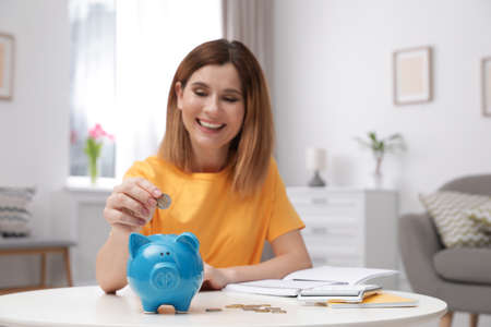 Woman putting coin into piggy bank at table in living room. Saving money Standard-Bild
