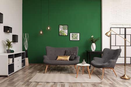 Modern living room interior stylish sofa near green wall 免版税图像