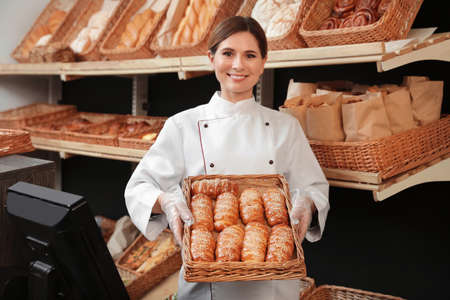 Professional baker holding tray with fresh buns in store 版權商用圖片