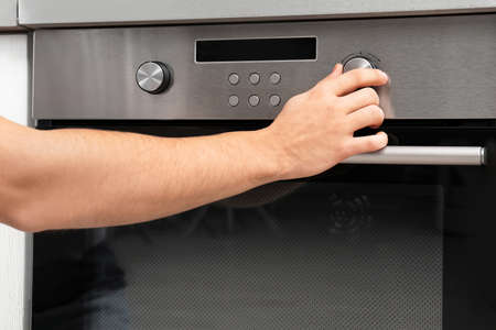 Young man adjusting oven settings in kitchen, closeup