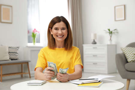 Smiling woman counting money at table indoors Stock Photo