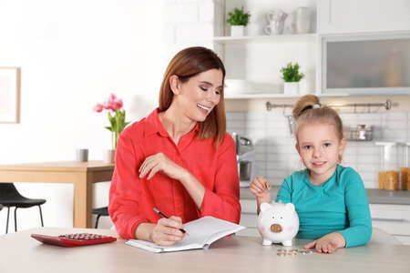Mother and daughter putting coin into piggy bank at table indoors. Saving money 版權商用圖片