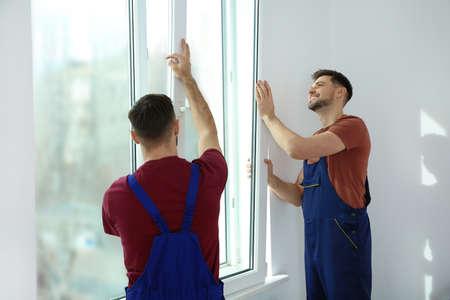 Construction workers installing plastic window in house Banco de Imagens