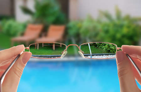 Woman looking through glasses, closeup. Improvement of vision after visiting ophthalmologist