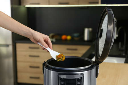 Young woman preparing food with modern multi cooker in kitchen Stock Photo