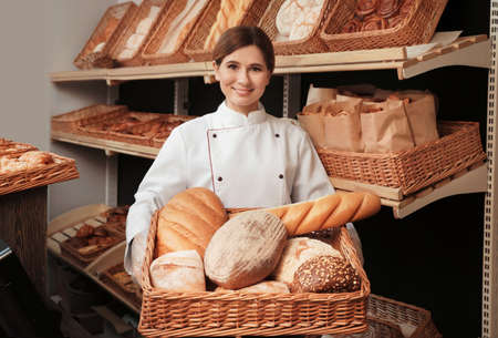 Professional baker with tray full of fresh breads in store Reklamní fotografie
