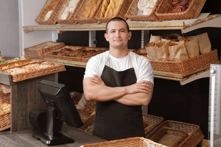 Portrait of professional baker at cashier desk near showcase in store