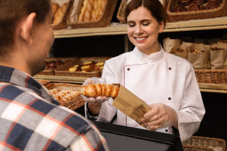 Baker putting fresh bun into paper bag in store