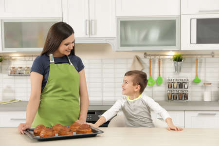 Son and mother with tray of oven baked buns at table in kitchen