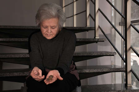 Poor upset mature woman with coins on stairs. Space for text Stok Fotoğraf