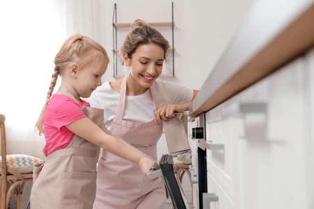Madre e hija horneando alimentos en el horno en casa Foto de archivo