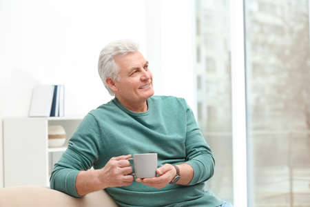 Portrait of mature man with cup of drink on sofa indoors Reklamní fotografie