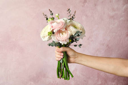 Woman holding bouquet with beautiful ranunculus flowers on color background