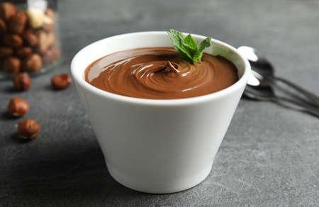 Keramikschale mit süßer Schokoladencreme und Minze auf dem Tisch