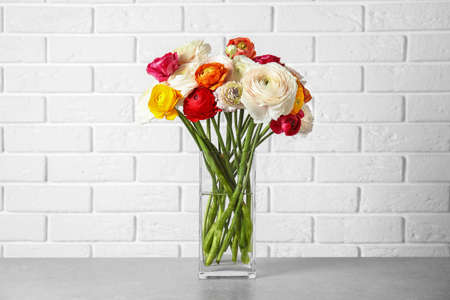 Vase with beautiful spring ranunculus flowers on table near brick wall