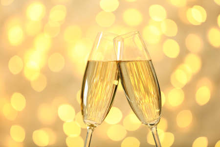 Clinking glasses of champagne against blurred lights
