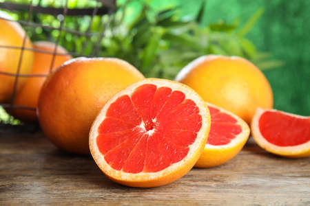 Fresh tasty grapefruits on table against blurred background