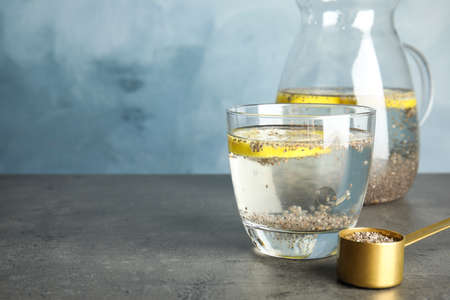 Glass of water with chia seeds and lemon on table. Space for text