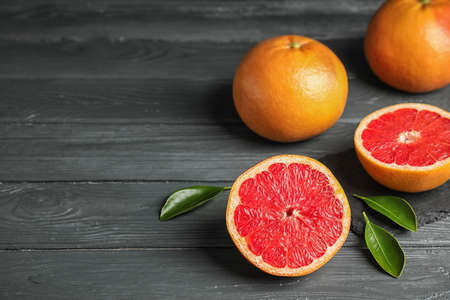 Fresh tasty grapefruits on table. Space for text Stock Photo