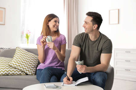Paar verwaltet das Budget, um Geld im Wohnzimmer zu sparen Standard-Bild