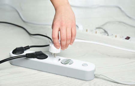 Woman inserting power plug into extension cord on floor, closeup with space for text. Electrician's professional equipment