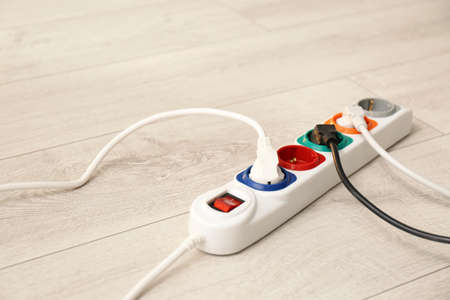Extension cord on floor, space for text. Electrician's professional equipment 스톡 콘텐츠