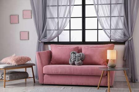 Comodo divano vicino alla finestra nell'interno moderno del soggiorno Archivio Fotografico
