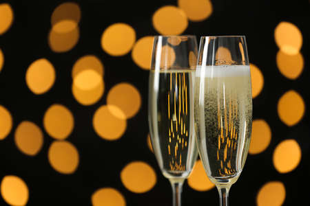 Glasses of champagne against blurred lights. Space for text