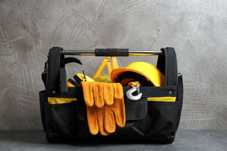 Black bag with construction tools on table Stock Photo