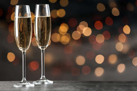 Glasses of champagne on table against blurred lights, space for text. Bokeh effect Imagens