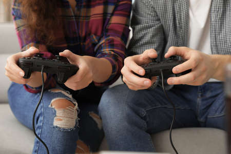 Young couple playing video games at home, closeup