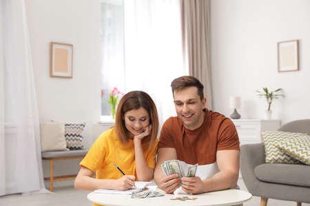 Couple counting money at table in living room