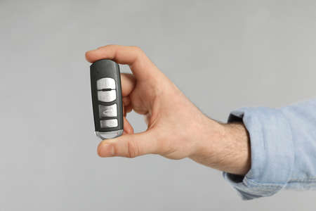 Young man holding car smart key on grey background, closeup 写真素材