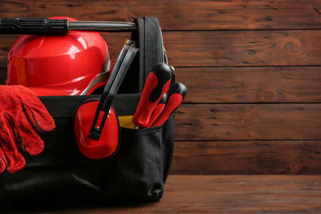 Black bag with construction tools on table against wooden background, space for text