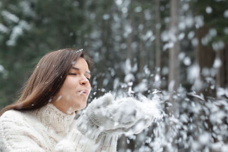 Young woman playing with snow outdoors. Winter vacation Foto de archivo