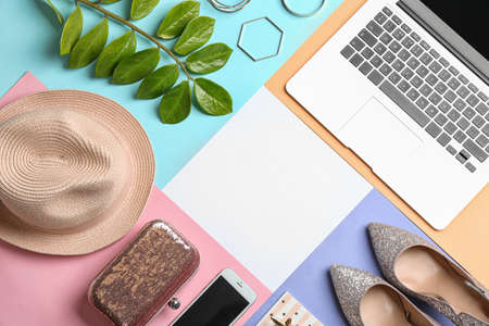 Flat lay composition with laptop, shoes, hat and space for text on color background. Fashion