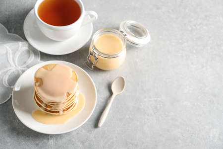 Composition with pancakes and condensed milk on grey background, space for text. Dairy product