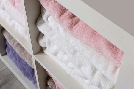 Colorful towels on shelves, closeup. Bathroom supplies Standard-Bild - 120650219
