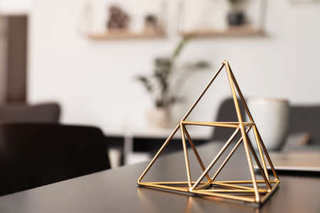 Decorative metal pyramid on table in room. Modern interior element