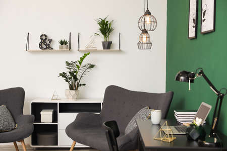 Interior moderno de la sala de estar con lugar de trabajo cerca de la pared verde