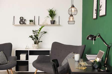 Moderner Wohnzimmerinnenraum mit Arbeitsplatz nahe grüner Wand