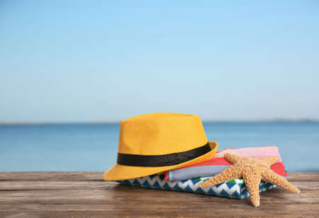 Different beach accessories on table against sea, space for text
