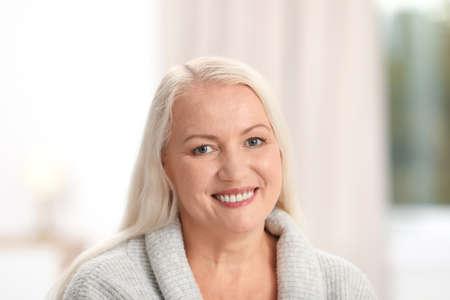 Portret van mooie oudere vrouw tegen onscherpe achtergrond Stockfoto