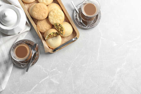 Flat lay composition with tray of cookies for Islamic holidays, cups and space for text on table. Eid Mubarak Stockfoto