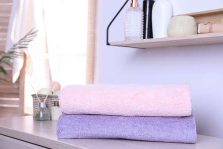 Stack of fresh towels on table in bathroom