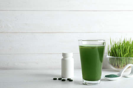 Glass of spirulina drink, pills and powder on table. Space for text 免版税图像