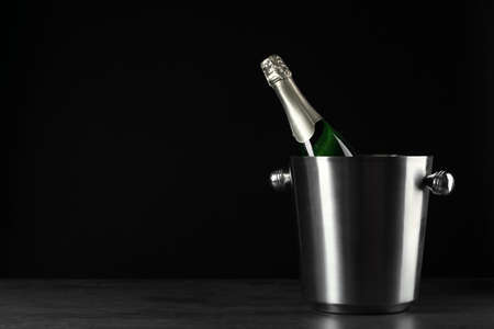 Bottle of champagne in bucket on black background. Space for text