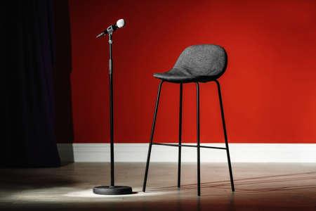Microfono e sgabello sul palco contro la parete colorata